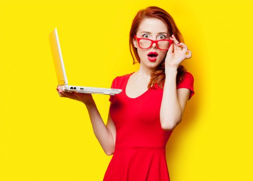 photo of beautiful young woman holding laptop on the wonderful yellow studio background